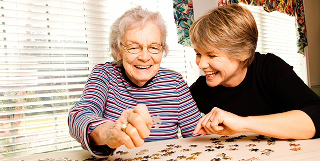 Happy elderly woman & volunteer working on a jigsaw puzzle together