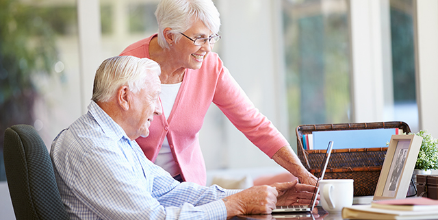 Smiling elderly couple on a computer together