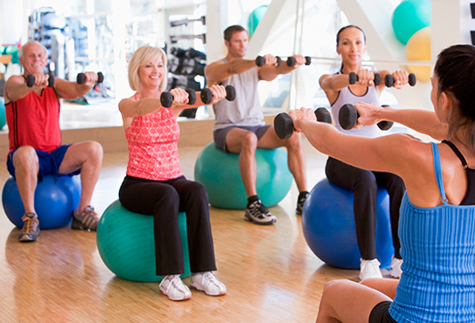 Elderly Group Exercise with Yoga Balls and Barbells